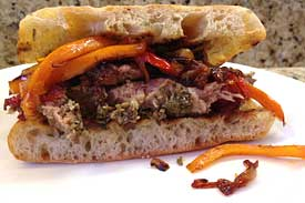 Slow-roasted Tuscan pork sandwich with caramelized onions and peppers