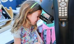 Young girl looking at the moon through a telescope.