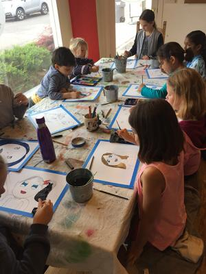 A class of young students sitting around a table using watercolors to paint in their line drawing self portraits