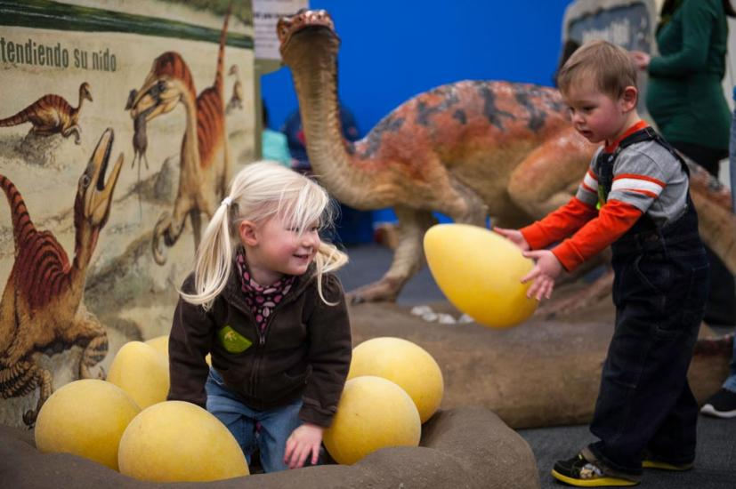 Young children playing in a dinosaur exhibit at the Bay Area Discovery Museum