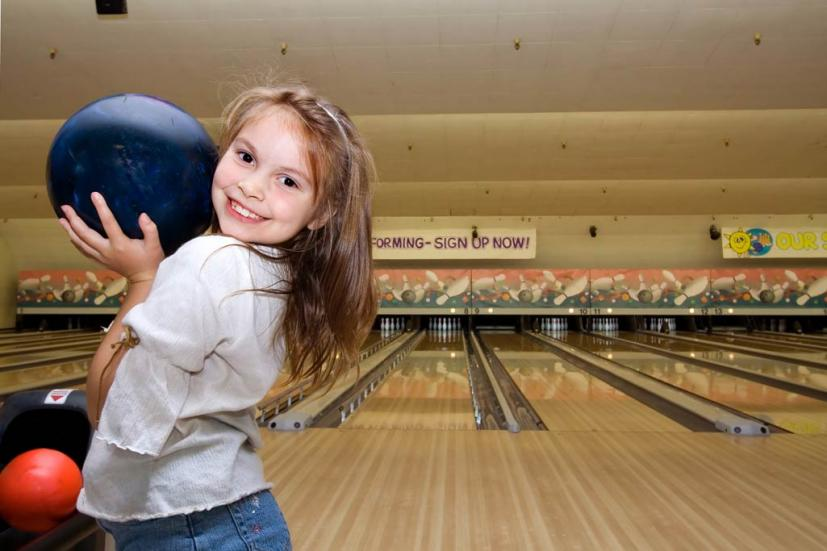 Child bowling at birthday party