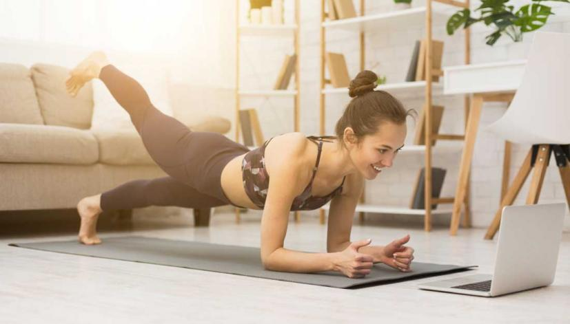 woman doing yoga with a laptop