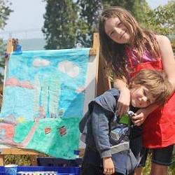 Two kids displaying their artwork