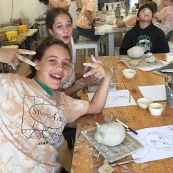 Three students smiling and having fun while creating pottery pieces in ceramic class at Studio 4 Art